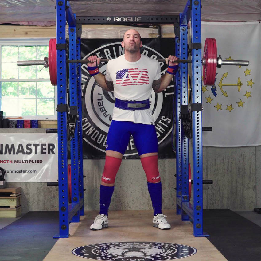 Brandon Campbell standing in the squat rackm showing off his strong legs