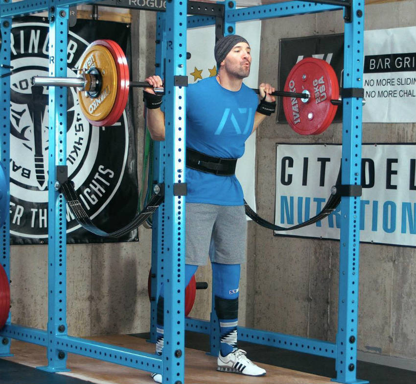 Brandon Campbell standing in squat rack, completing a squat with his large chest puffed out