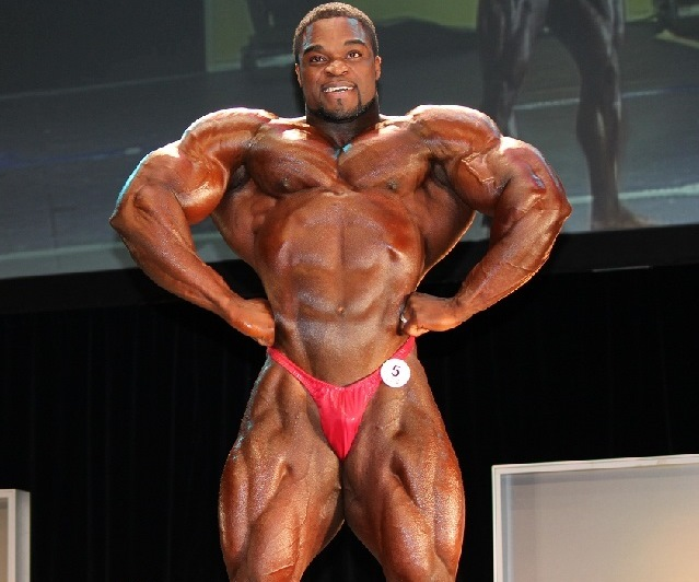 Brandon Curry in the front lat spread pose in red bodybuilding underwear, showing is big and muscular physique