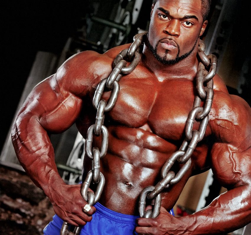 Brandon Curry with chains around his neck, flexing his shirtless upper body