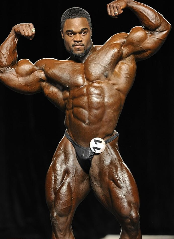 Brandon Curry on the stage, in a front double biceps pose, displaying his impressive conditioning to the judges