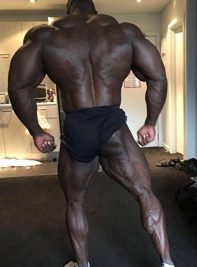 Brandon Curry standing in black shorts, showing his incredible back, arms, and legs development