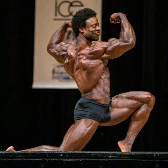 Breon Ansley posing with confidence at the New York Pro, tensing his large biceps