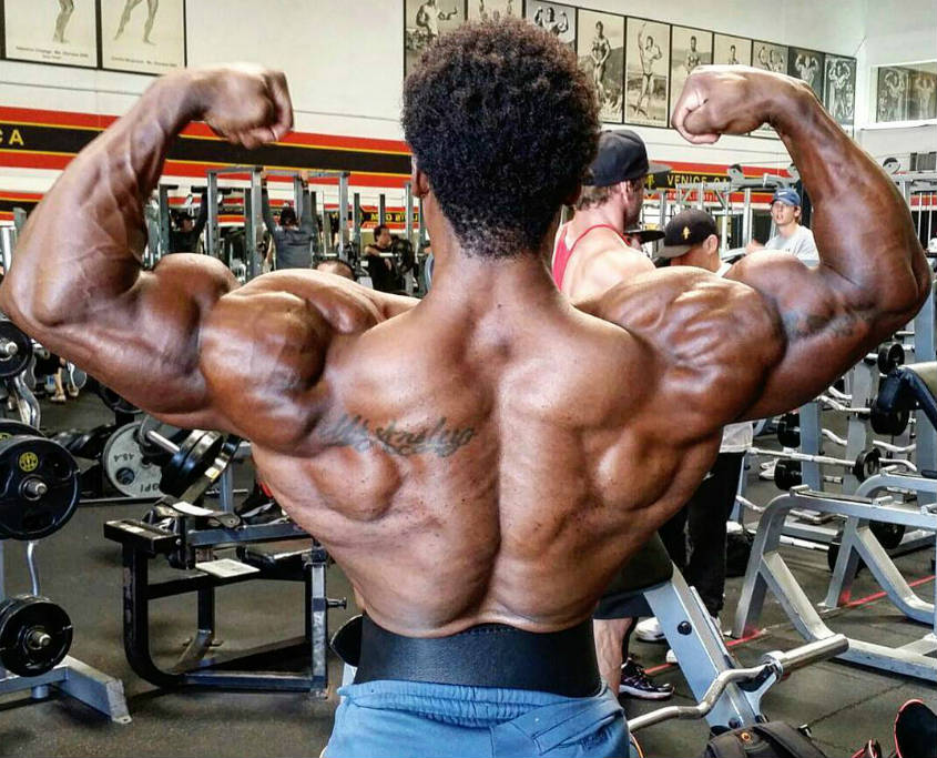 Breon Ansley showing his well-built back and shoulder muscles in the gym