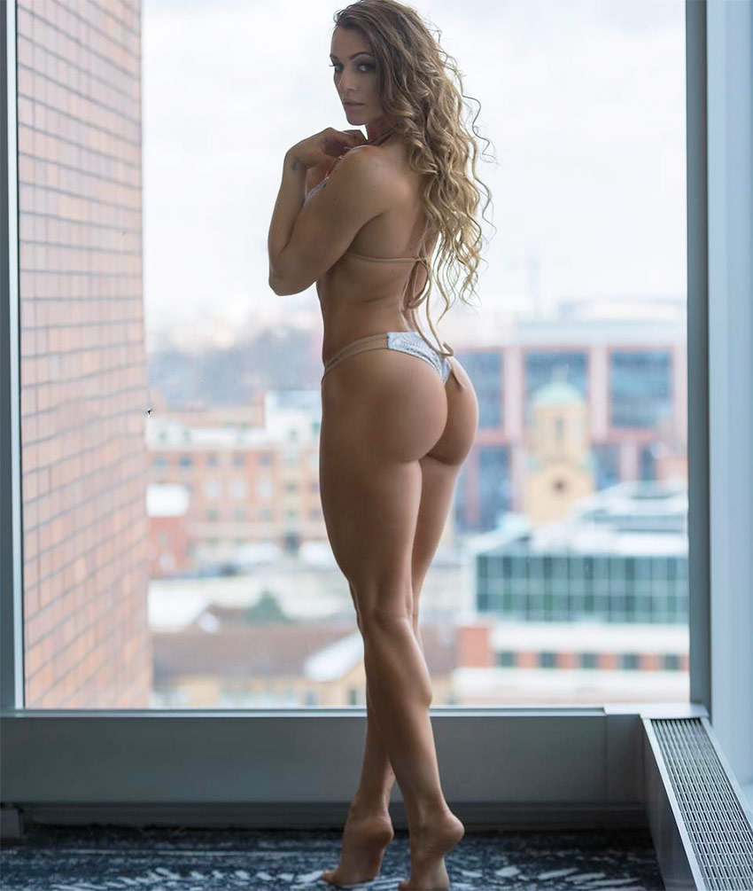 Caroline Campos posing next to the window of a high rise building, displaying her shapely glutes and legs.
