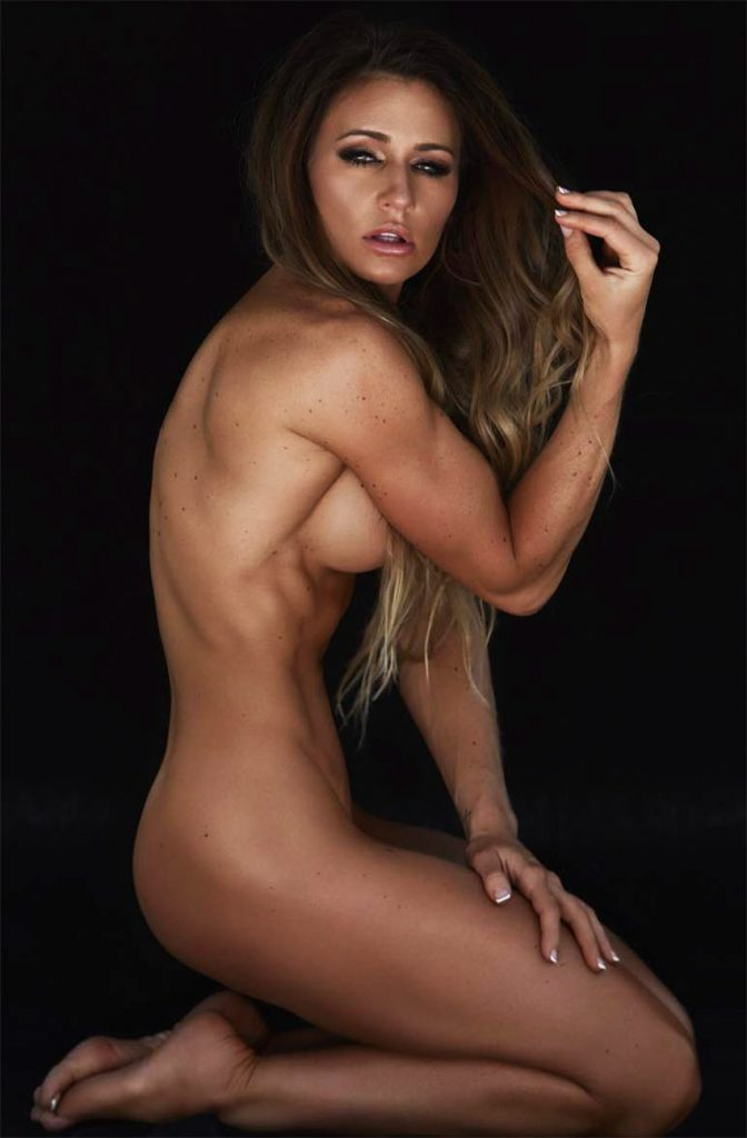 Caroline Campos posing in front of a black background naked, tensing her biceps and displaying her muscular definition on her figure.