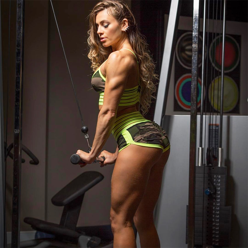 Caroline Campos posing while performing tricep pulldowns, displaying the muscularity on her arms and glutes.