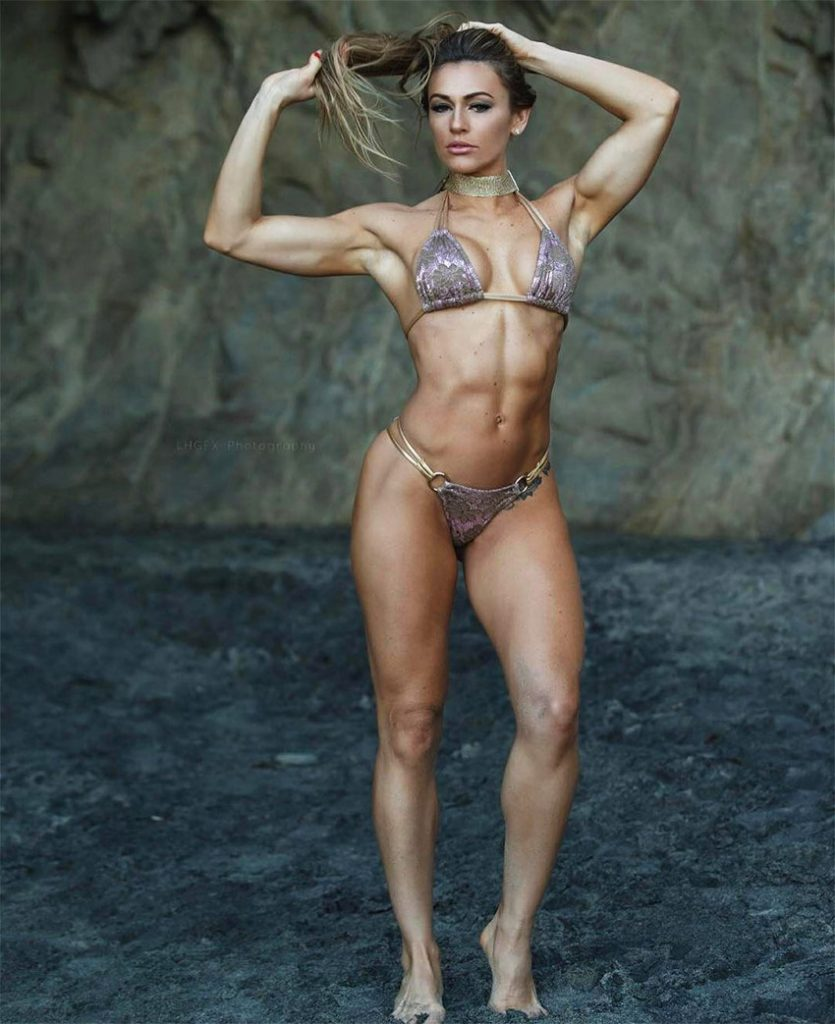 Caroline Campos posing in a bikini in a cave, tensing her bicep and showing her shredded abs and figure.