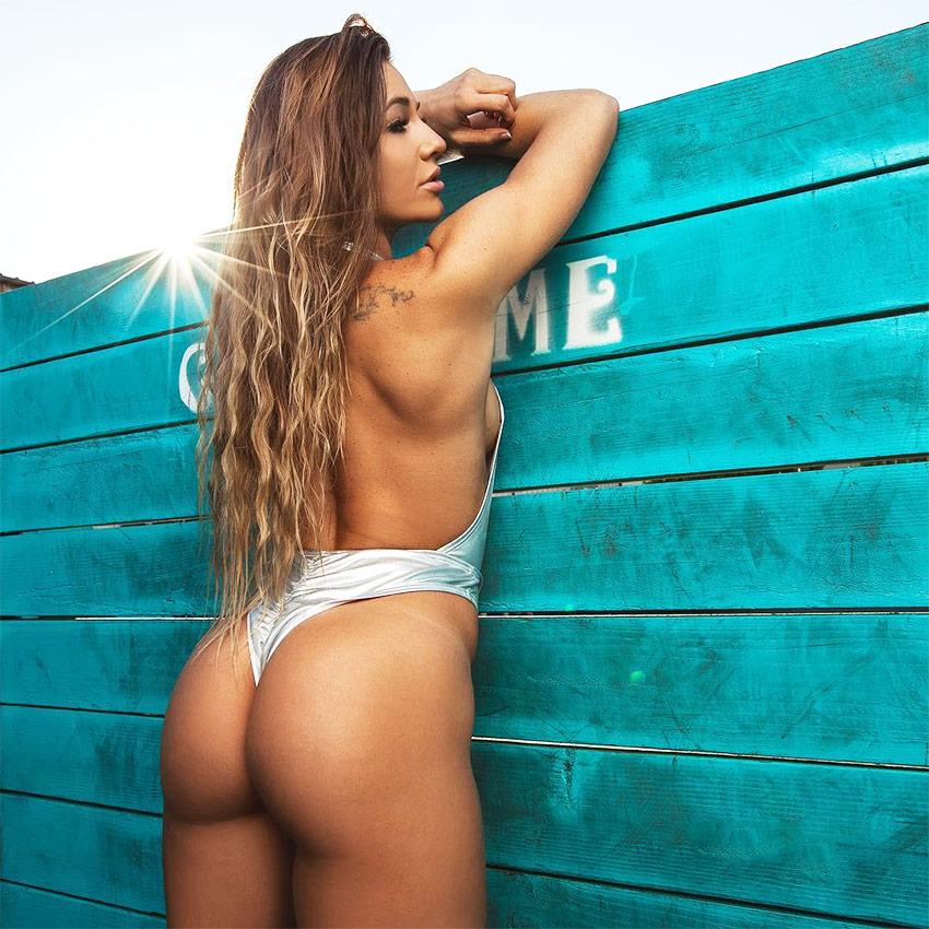 Caroline Campos leaning on a green wooden fence in a swimsuit, displaying her incredibly shaped glutes and legs.