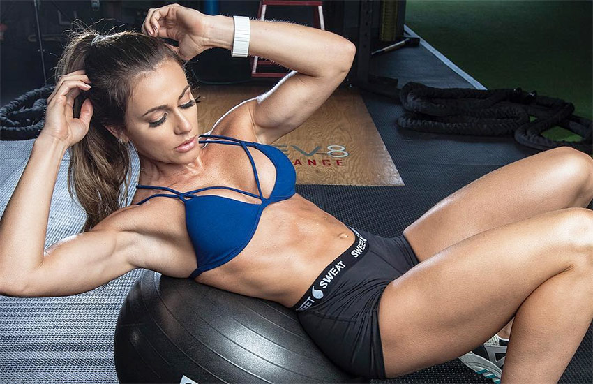 Caroline Campos on a workout ball performing sit ups to enhance her shredded abs, while in sportswear in the gym.