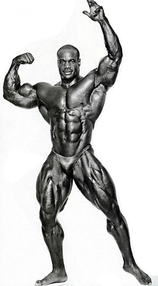 Chris Cormier posing, showing his massive quads, ripepd abs and large chest and arms