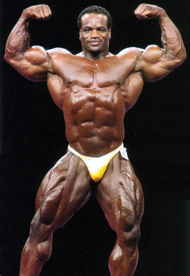 Chris Cormier posing at a competition, showing his large quads, ripped abs and large bulging biceps