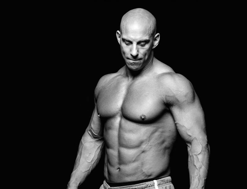 Christian Thibaudeau showing his large, toned abs and pectorals