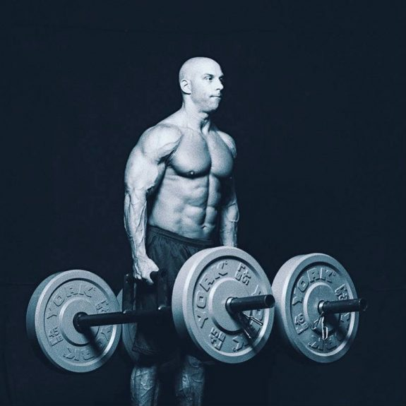 Christian Thibaudeau walking with two weighted bars, showing his large chest, abs and shoulders