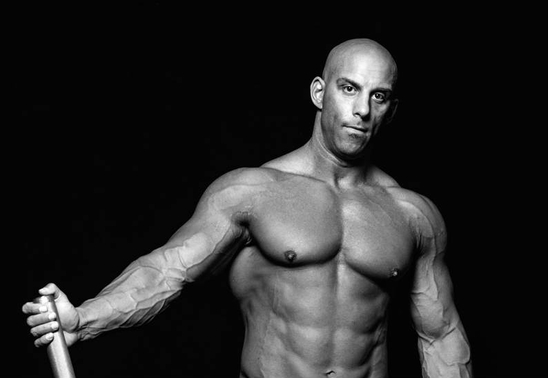 Christian Thibaudeau showing his large abs, chest and vascular arms