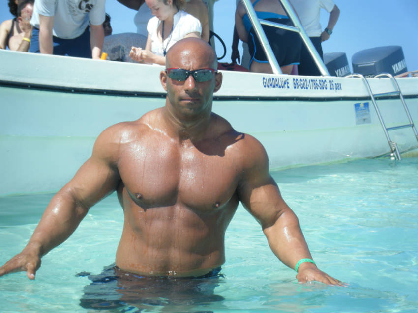 Christian Thibaudeau swimming in the sea, howing his large arms, shoulders and toned abs