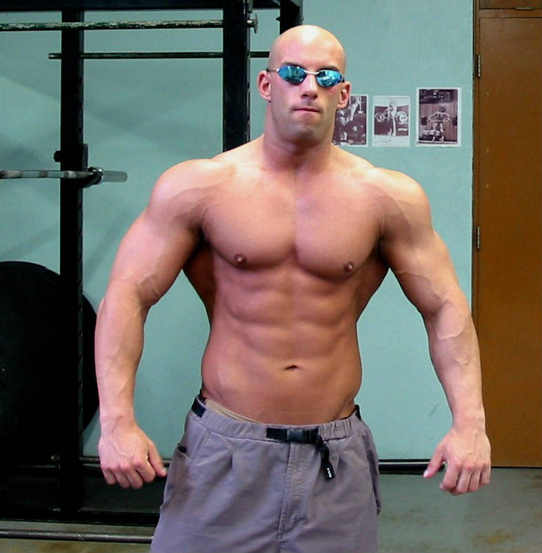 Christian Thibaudeau showing his large arms, ripped abs and vascular delts