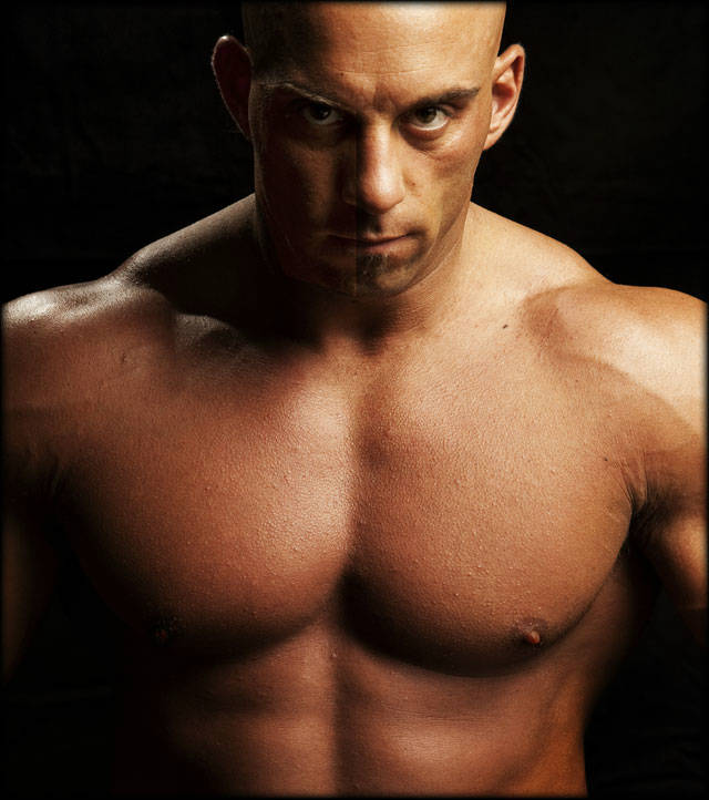 Christian Thibaudeau showing his large chest and abs in close up eye contact shot