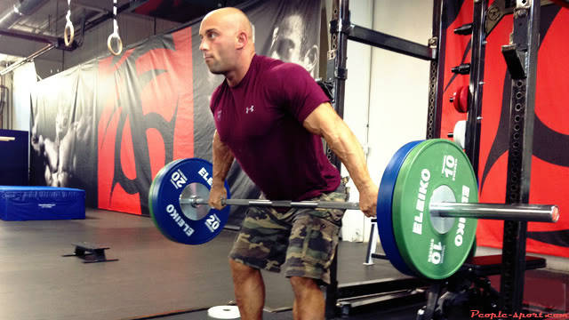 Christian Thibaudeau compelting a snatch lift, showing his large arms and chest