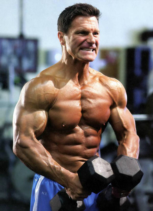 Clark Bartram listing two dumbbells and showing his large arms, chest and abs