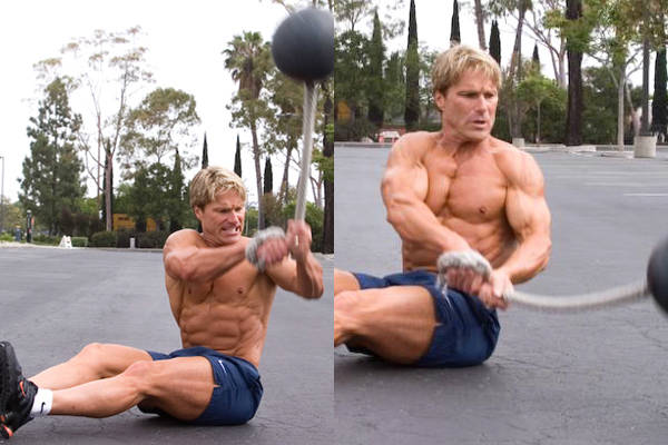 Clark Bartram completing an oblique twist with a ball on a rope, showing his abs, obliques and chest