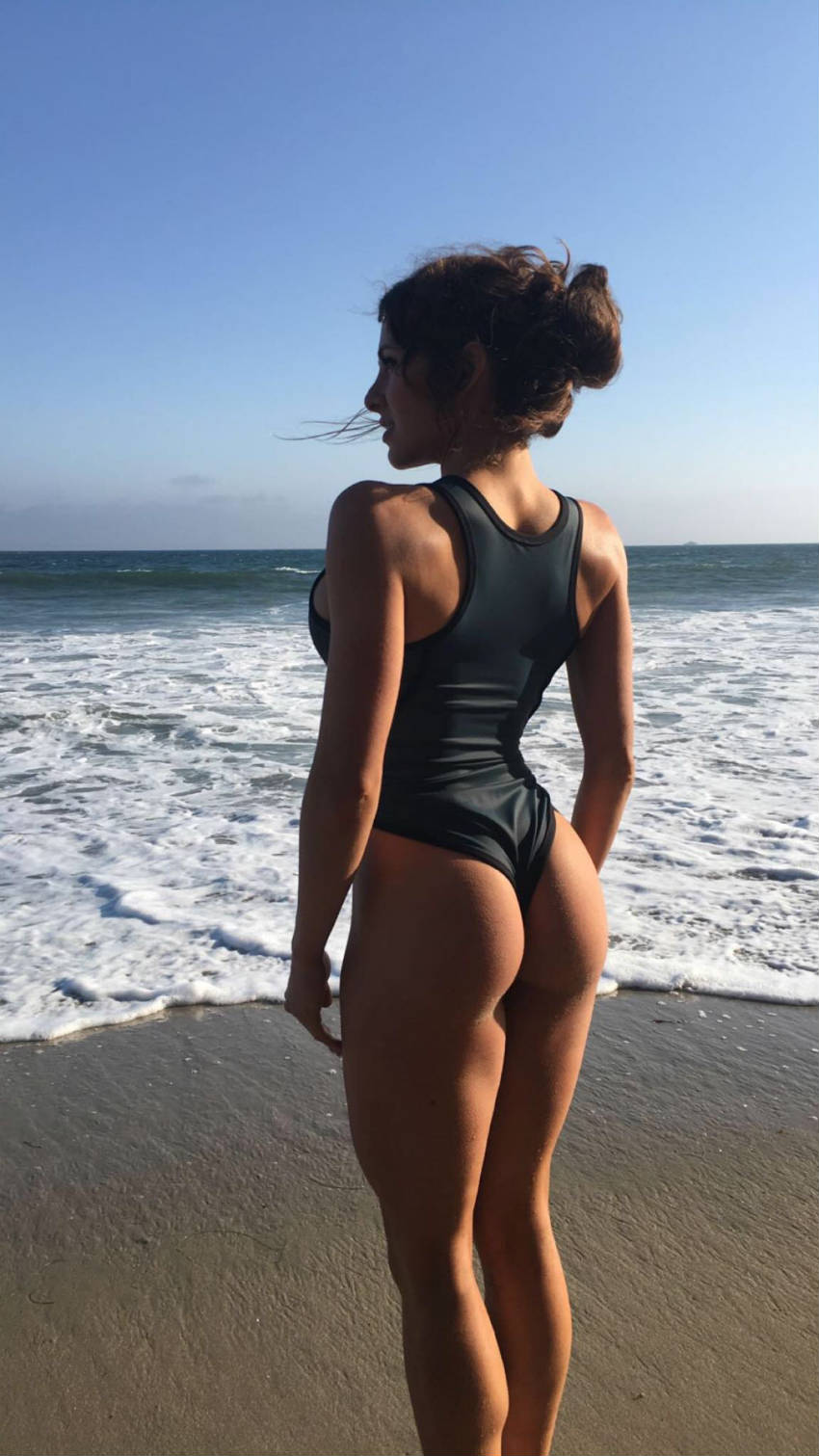Courtney King syanding on the beach, showing off her toned glutes