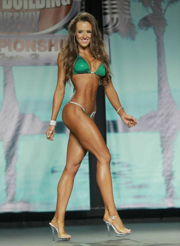 Courtney King posing at a competition, showing off her abs, toned legs and toned arms