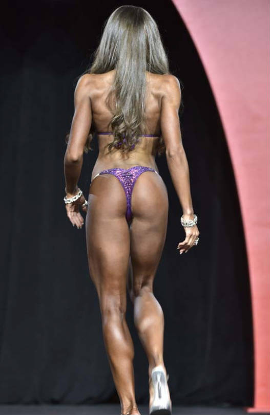 Courtney King showing her glutes and toned delts and back to the judges at a competition