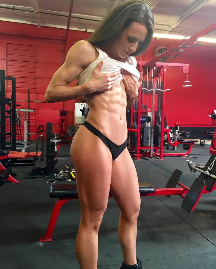 Courtney King lifting up her top to show her ripped abs in the gym