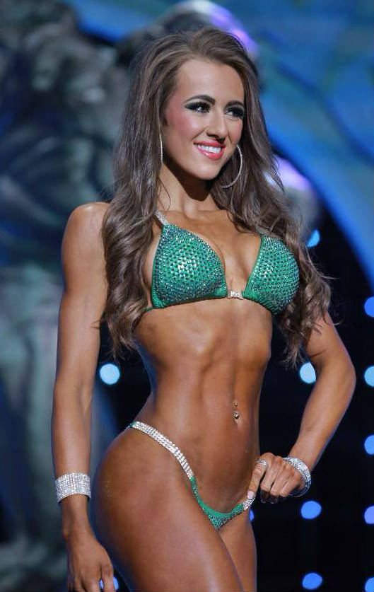 Courtney King posing at a competition, showing her abs and toned arms