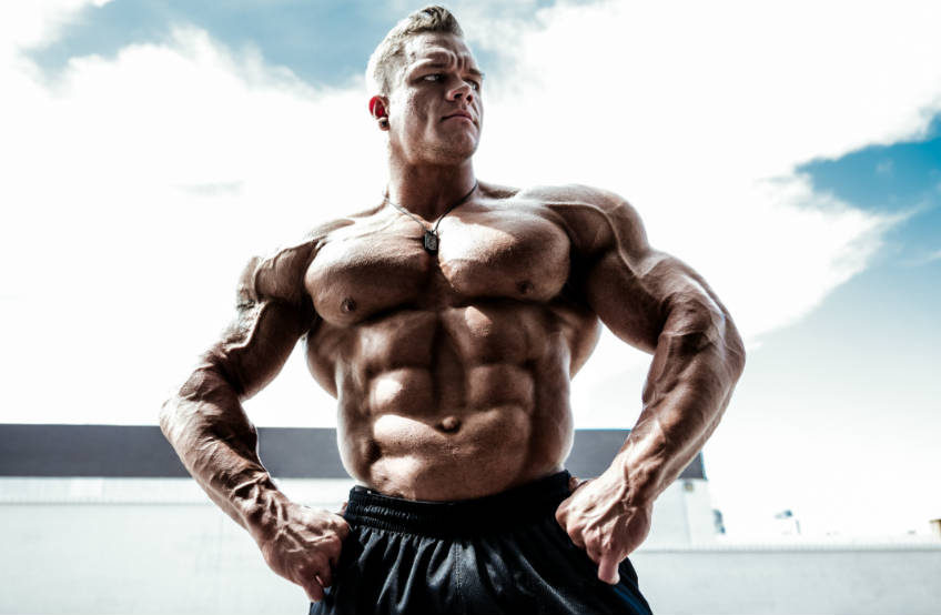 Dallas Mccarver posing with his hands on his hops, showing off his ripped abs and massive chest