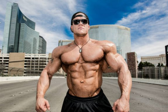 Dallas Mccarver posing in the street, showing his ripepd and well-built abs, large chest and huge delts