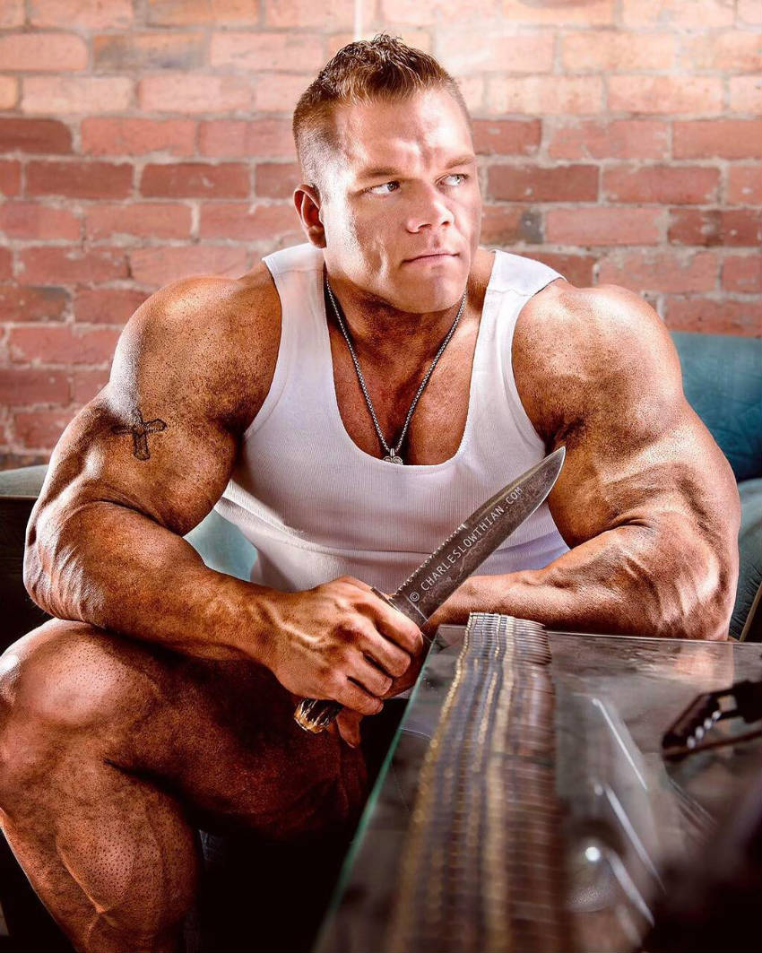 Dallas Mccarver sitting holding a knife, showing his large arms and legs