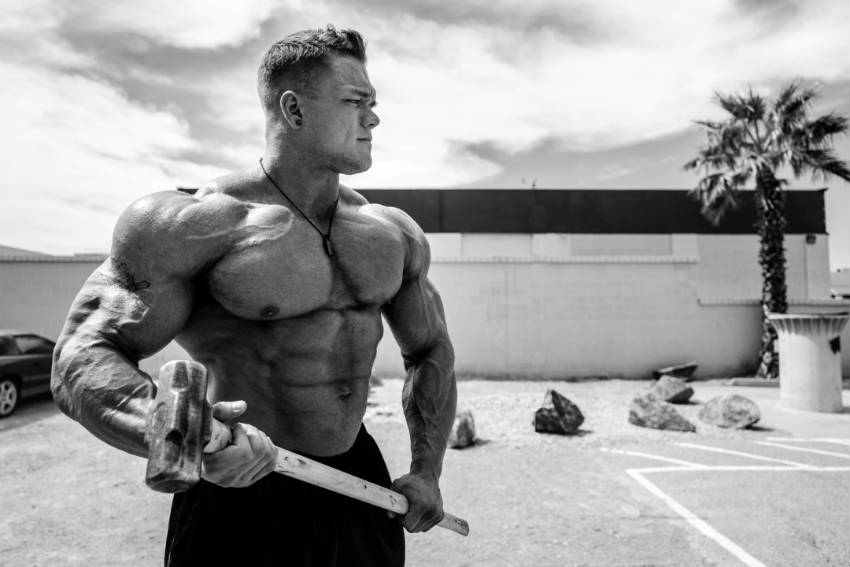 Dallas Mccarver standing with a sledge hammer, showing his large chest, arms and ripped abs