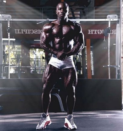 Damion Ricketts flexing his muscles in the gym wearing gym white gym shorts looking lean and muscular