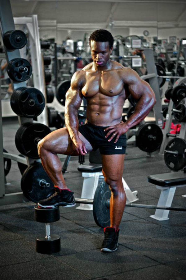 Daron Lytle standing on a dumbbell in the gym, showing his ripepd abs, large arms and chest and toned legs