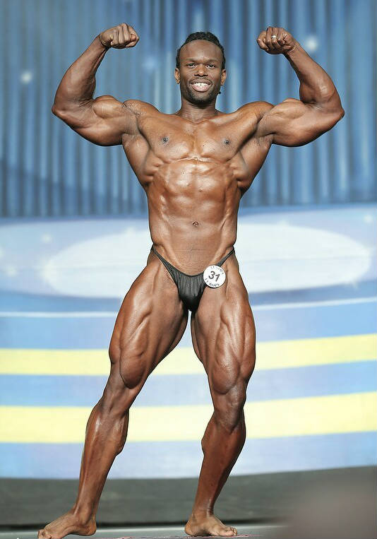Daron Lytle posing ta a competition, showing his abs, large quads and biceps