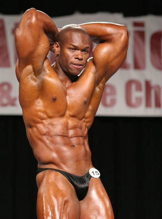 Daron Lytle posing at a competition, showing his ripped abs and large chest