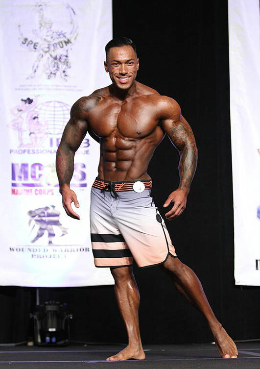 Dean Balabis posing at a physique competition, showing off his ripped abs, tapered waist and large delts