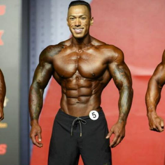Dean Balabis showing his ripped abs and toned chest at a contest