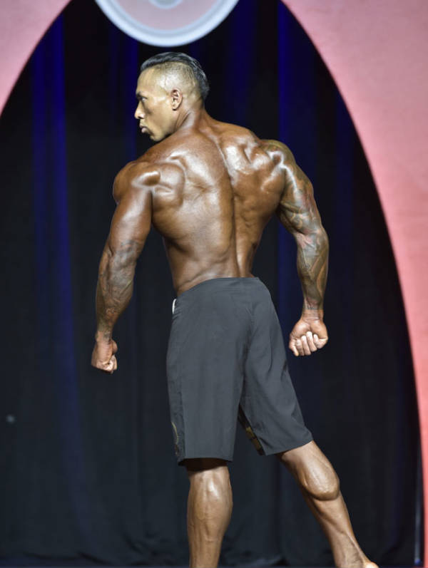 Dean Balabis showing his back and calves at a competition, displaying his hard work to the judges
