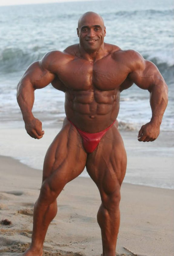 Dennis James standing on the beach, showing his large chest, arms and quads