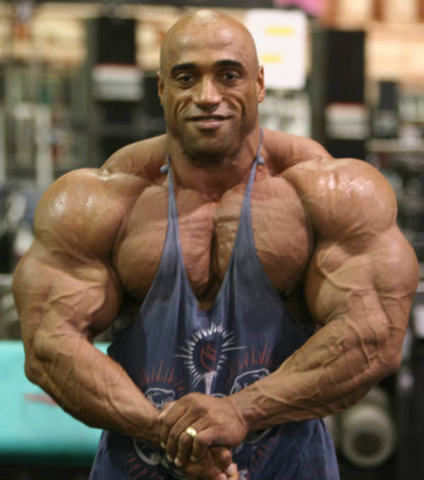 Dennis James showing his large, vascular arms and pumped chest