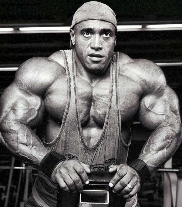Dennis James lying on an incline bench, showing his large arms and toned pectorals
