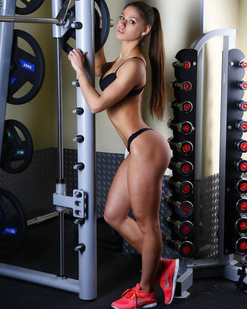 Diana Volkova leaning against a smith machine in a black bikini, showing her attractive physique from the side