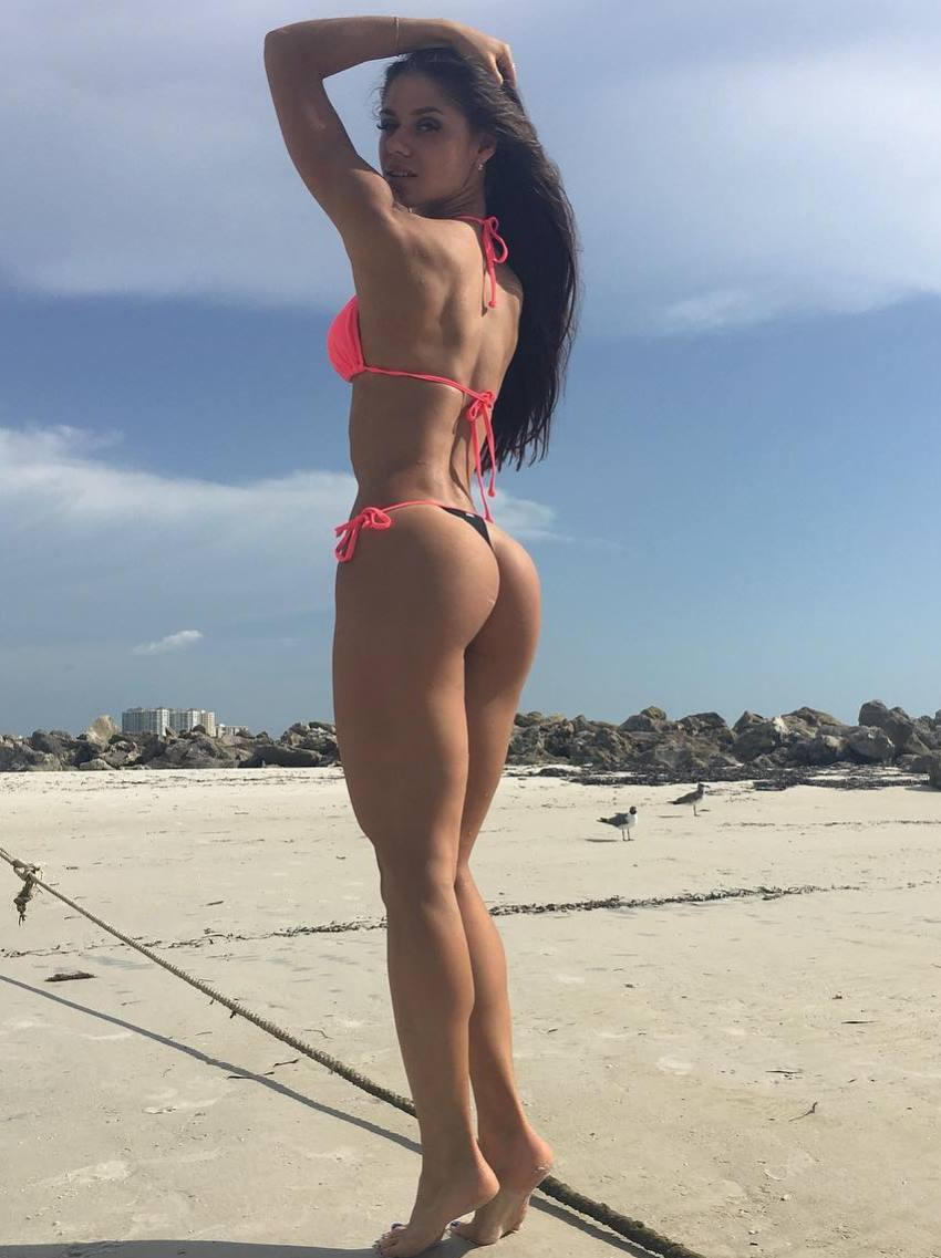 Diana Volkova showing her tones legs, glutes and back in a pink swimsuit