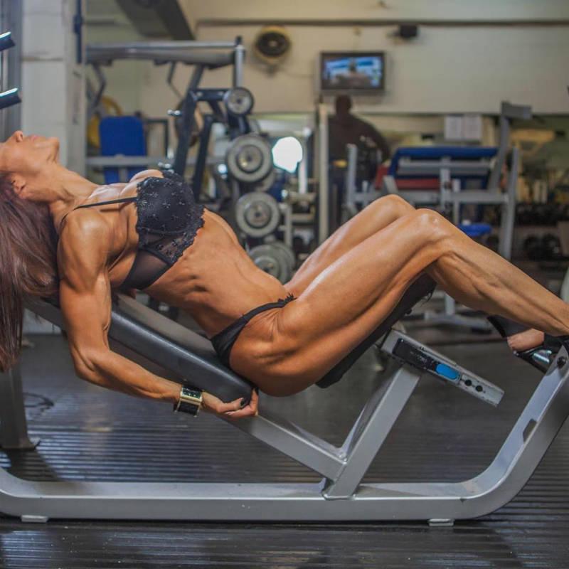 Donna De Lisser sitting on an incline bench in a bikini flexing her full body