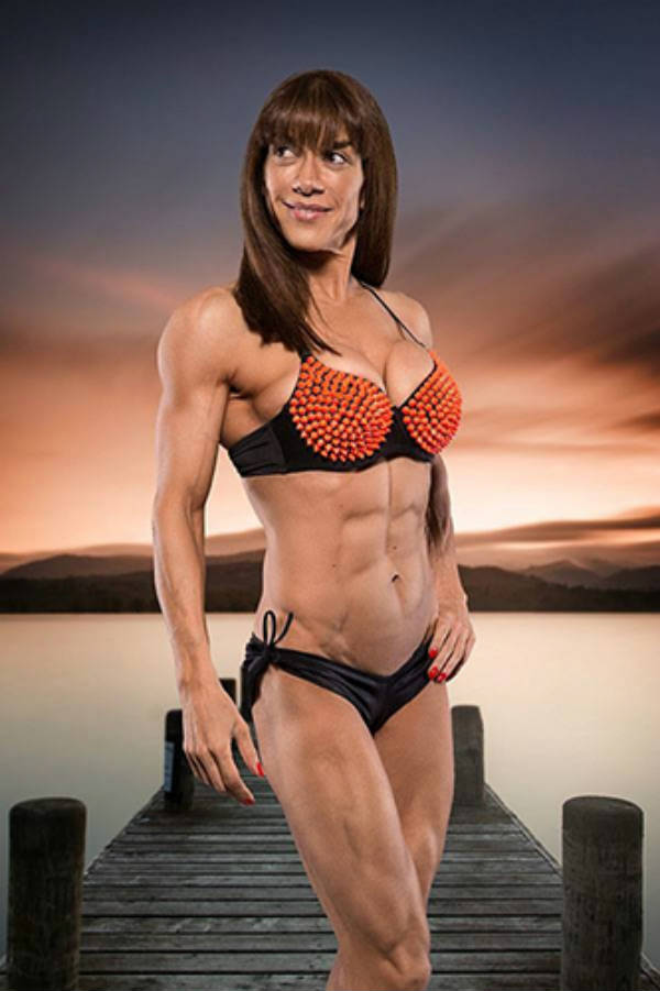 Donna De Lisser standing in front of a green screen. displaying her abs and big deltoids