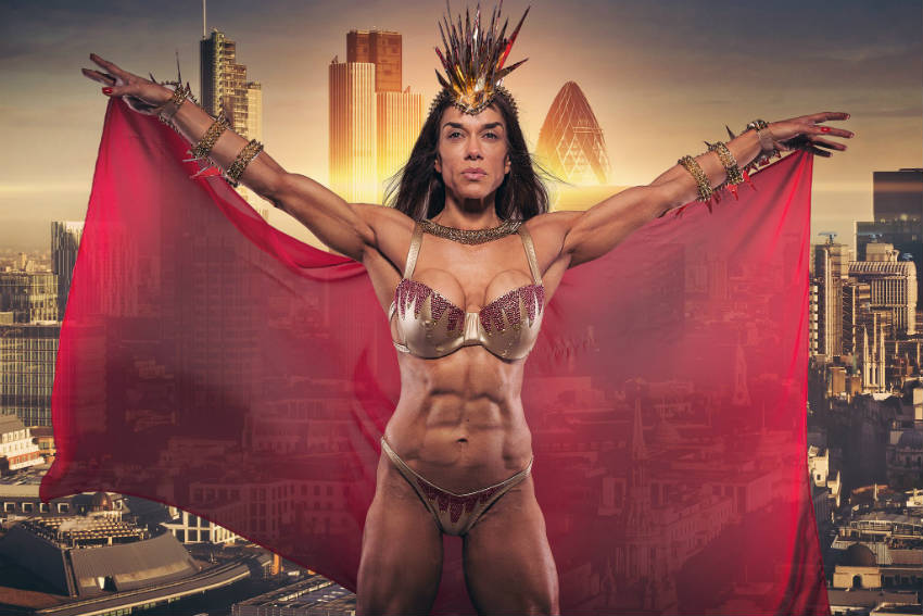 Donna De Lisser standing in front of a green screen of London, wearing a cape and showing off her ripped abs