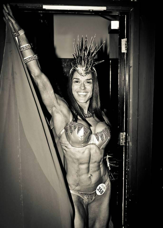 Donna De Lisser showing her ripped abdominal muscles and large arms while wearing a carnival themed outfit